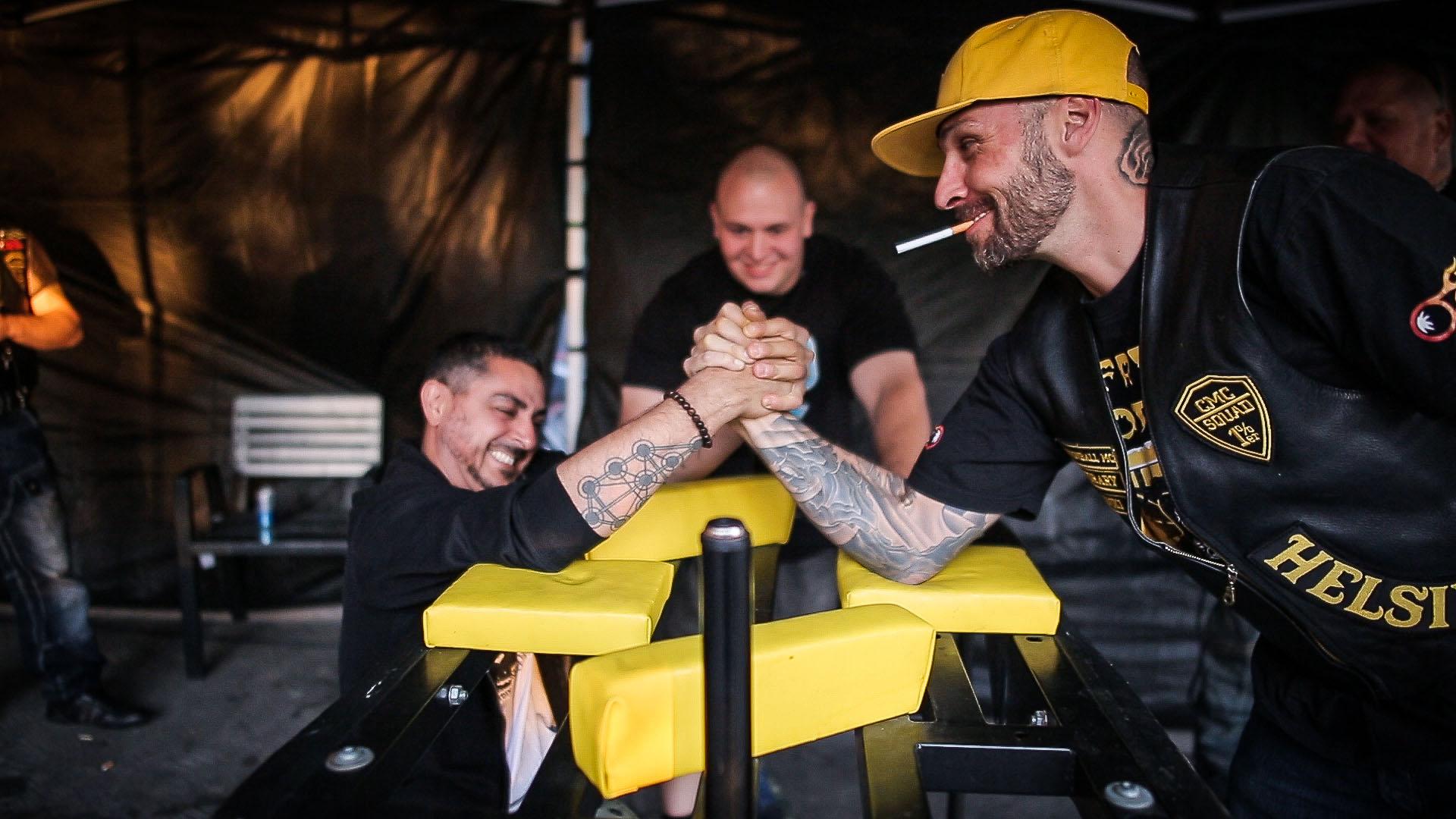 Arman Alizad vääntää kättä Cannonball-moottoripyöräkerhon jäsenen kanssa.