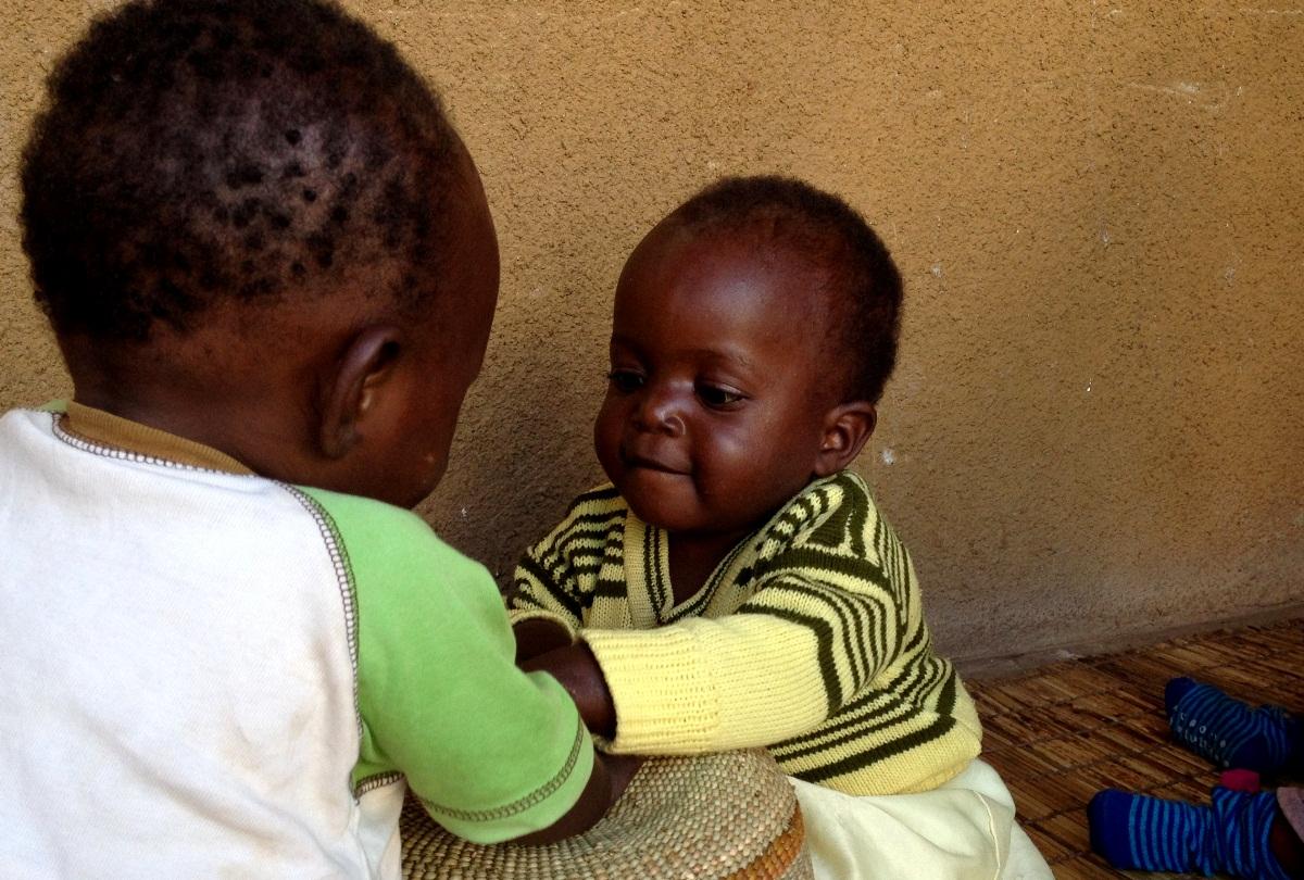 Emily (kasvot kameraan päin) leikkii rummulla Mufindin lastenkylässä.