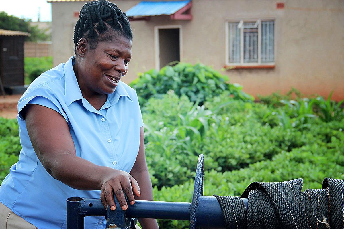 Florence Mbidzo nostaa vettä uudesta kaivostaan. Kuva: Iika Vehkalahti
