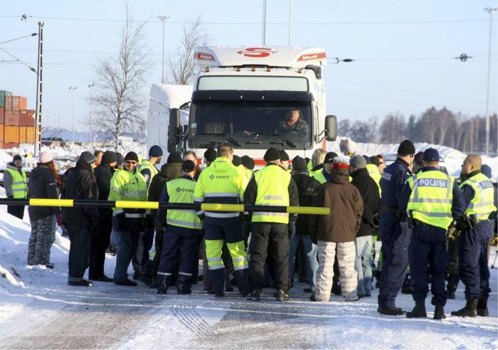 ◼Lakkoilevat ahtaajat yrittävät pysäyttää venäläisen rekan Mussalon  satamassa maaliskuussa 2010.  maaliskuuta 2010.  Ahtaajat vastustavat sitä, että töitä on pyritty jatkamaan muiden kuin ahtaajien voimin. Ahtaajat yrittivät estää venäläisen rekan pääsyn liikkeelle. LEHTIKUVA / RAIMO POUTANEN