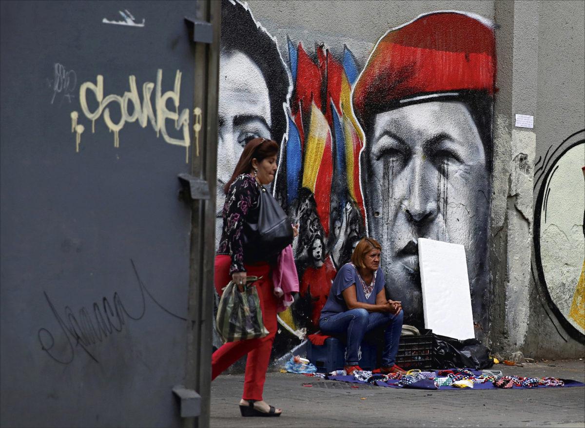 ◼Katukauppias myy tuotteitaan entistä  presidenttiä Hugo Chávezia kuvaavan graffitin edessä  Caracasissa.