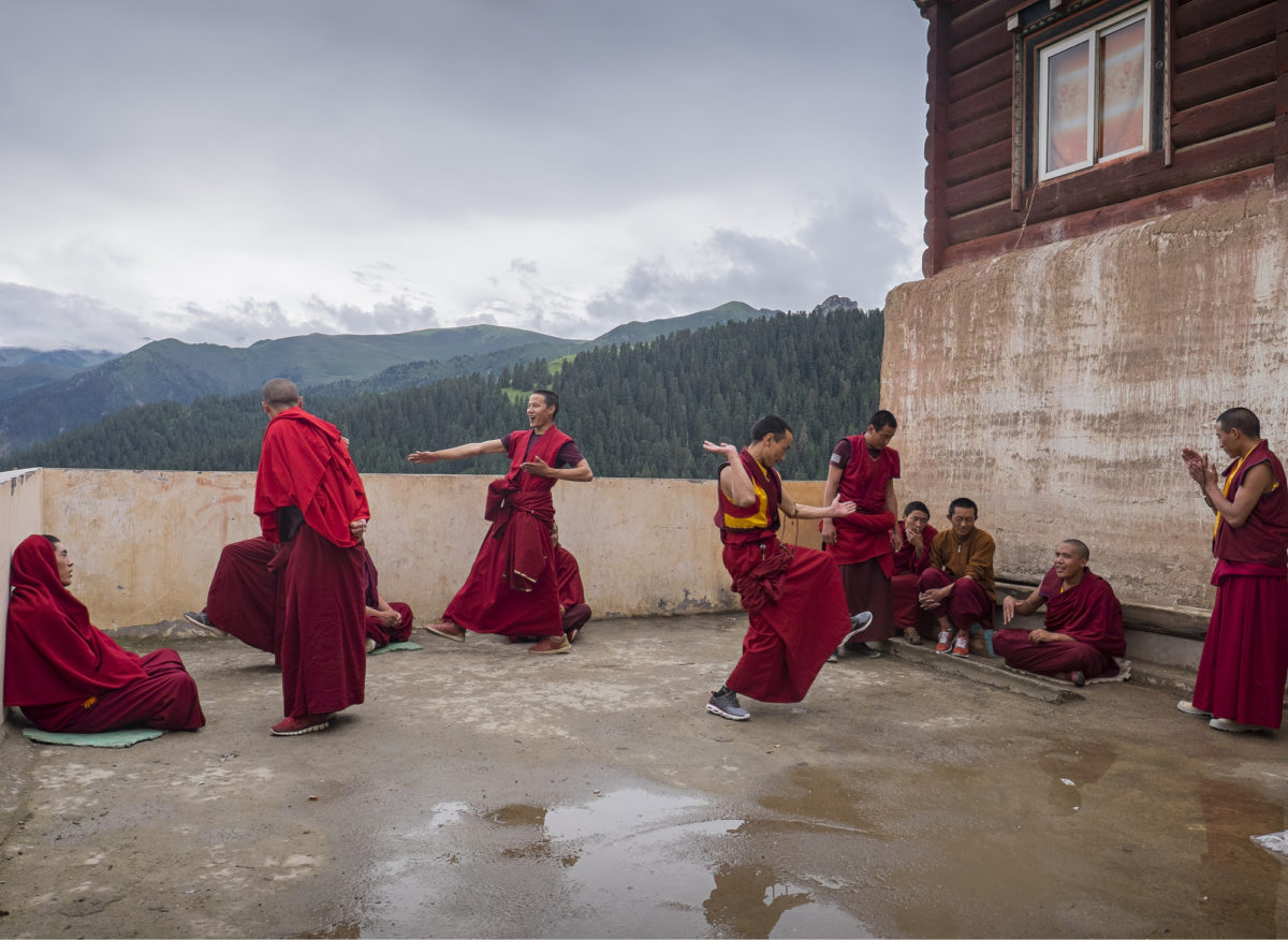 VÄITTELYHARJOITUS. Uskonnolliseen traditioon liittyvä filosofinen väittely on värikästä kuultavaa ja nähtävää. Munkit harjoittelevat oikeita otteita ja käsien läiskäytystä väittelyopiston terassilla Pelpungin luostarissa Khamissa.