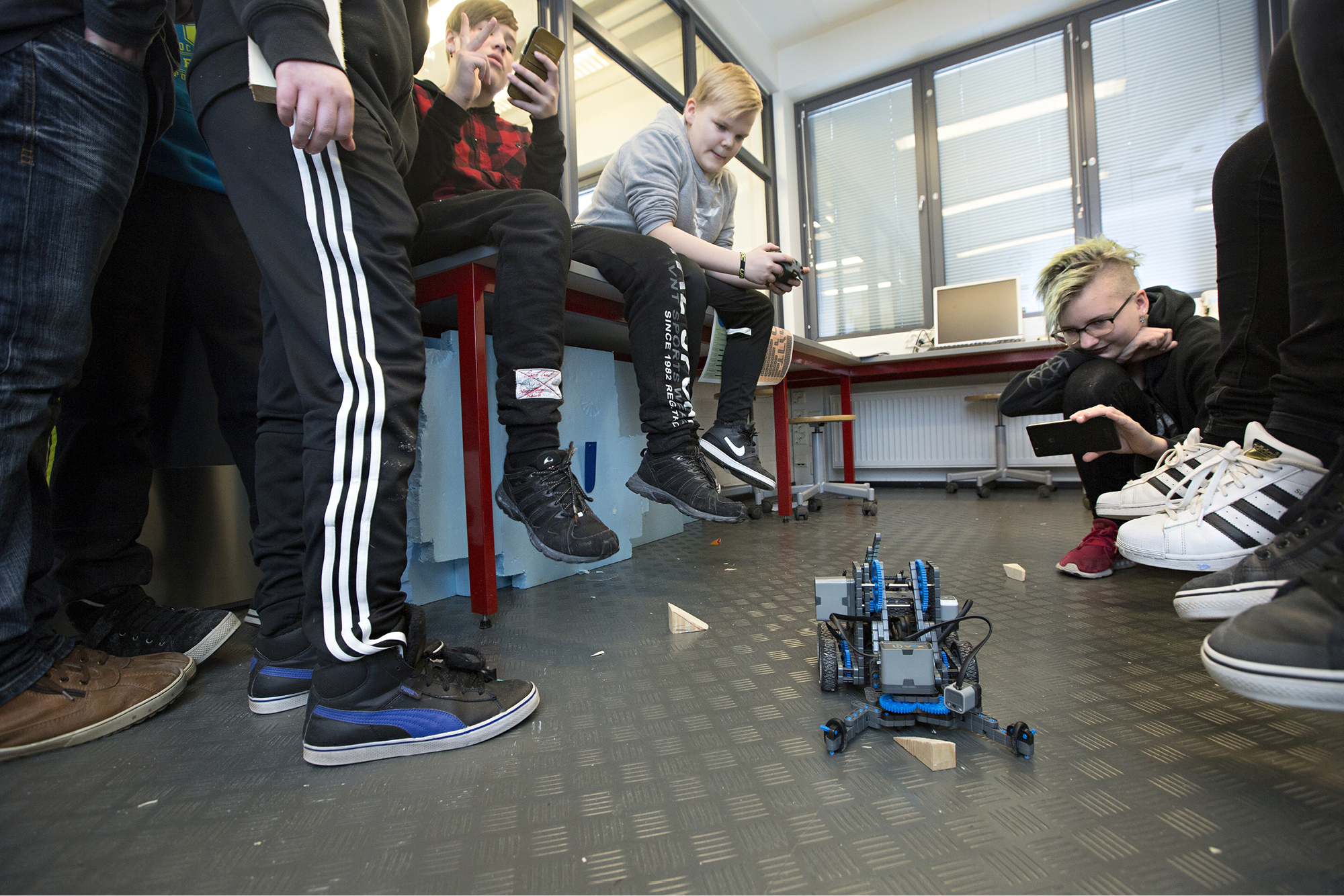 Teknisen työn kolmoistunnin loppukevennys. 7A:n Rasmus (vas.), Teemu ja Katri kisaavat, kuka nopeimmin kaataa palikat ohjelmoitavalla Vex-robotilla.