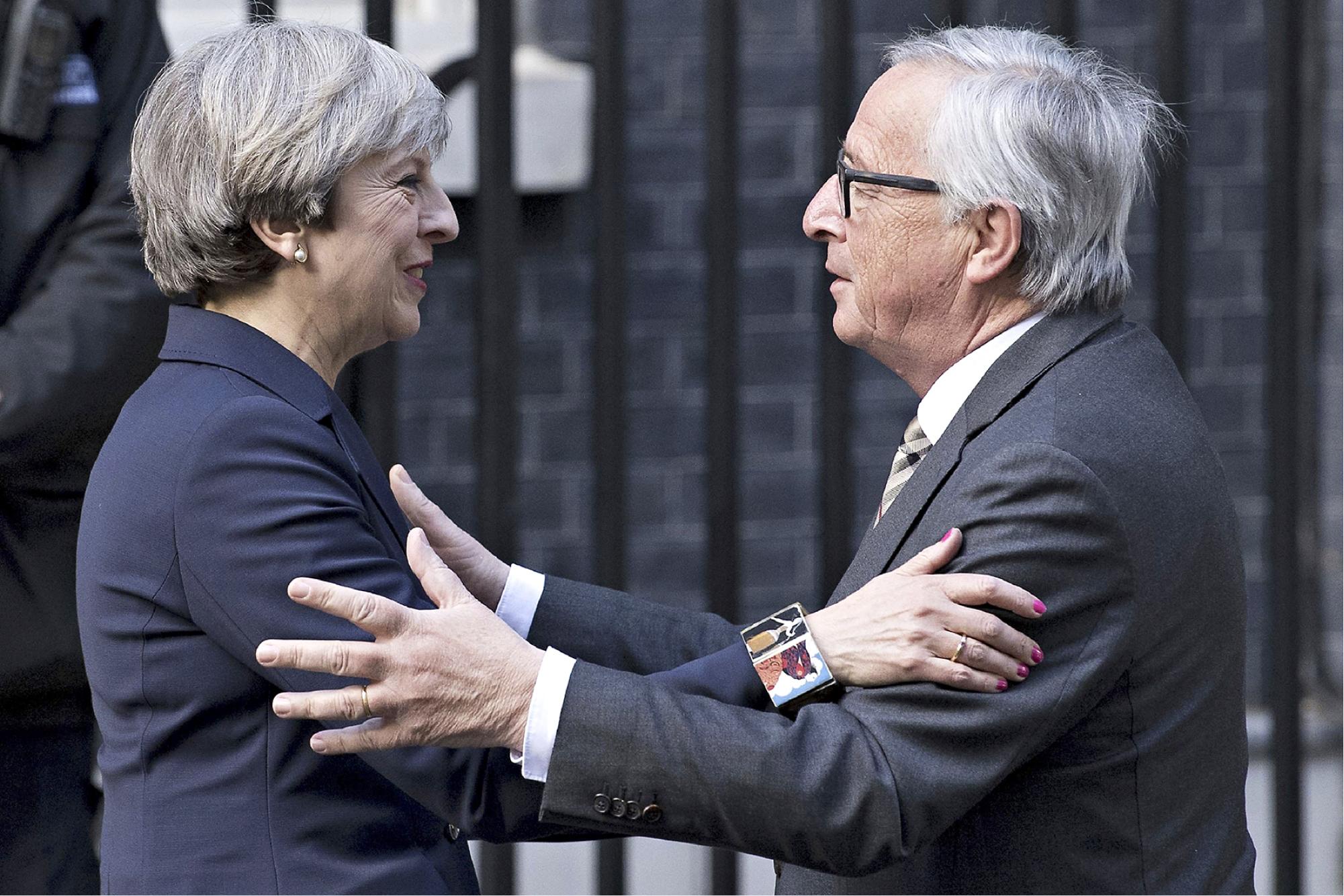Theresa May ja EU-komission Jean-Claude Juncker tervehtivät toisiaan ennen illallista Lontoossa 26.4.