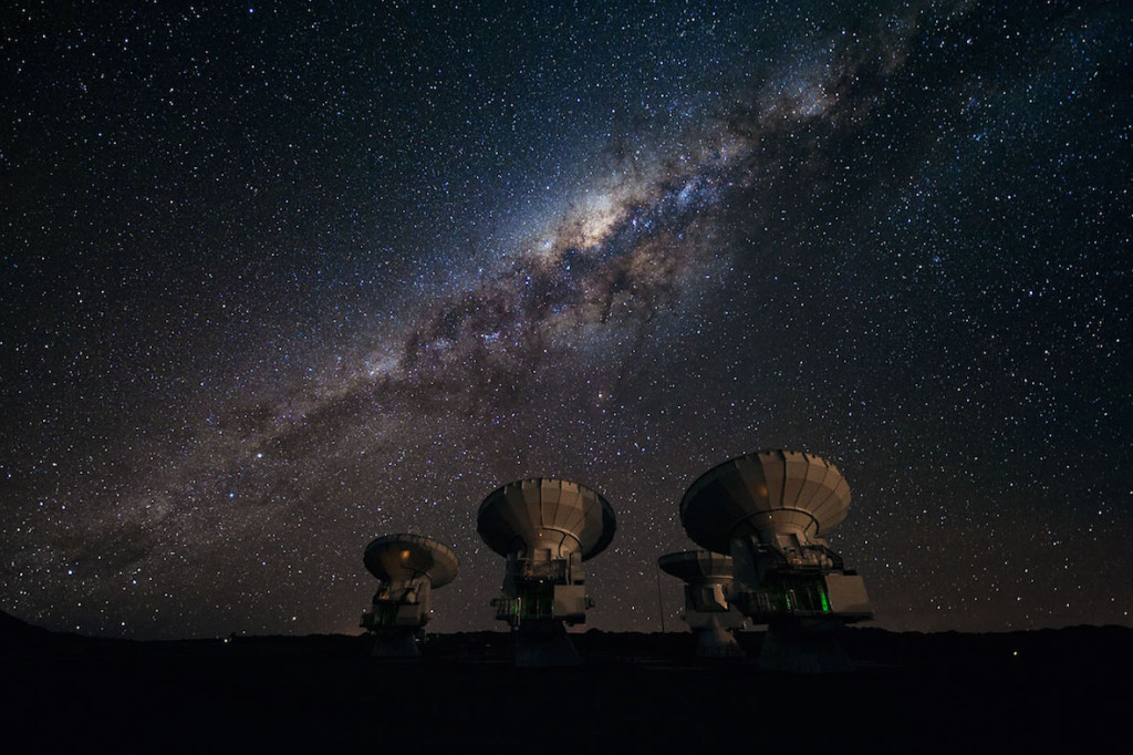 Four of the first ALMA antennas at the Array Operations Site (AOS), located at 5000 metres altitude on the Chajnantor plateau, in the II Region of Chile. Three of them — those which are pointing in the same direction — are being tested together as part of the ongoing Commissioning and Science Verification process. Across the image in the background is the impressive plane of the Milky Way, our own galaxy, here seen looking toward the centre. The centre of our galaxy is visible as a yellowish bulge crossed by dark lanes. The dark lanes are huge clouds of interstellar dust that lie in the disc of the galaxy. While opaque in visible light, they are transparent at longer wavelengths, such as the millimetre and submillimetre radiation detected by ALMA. ALMA, the Atacama Large Millimeter/submillimeter Array, is the largest astronomical project in existence and is a truly global partnership between the scientific communities of East Asia, Europe and North America with Chile. ESO is the European partner in ALMA.