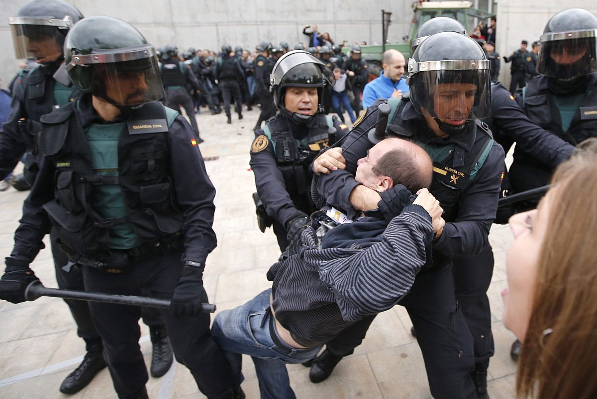 Espanjalaiset mellakkapoliisit poistivat miehen äänestyspaikan ulkopuolella Sant Julià de Ramisin kylässä Kataloniassa 1. lokakuuta 2017.