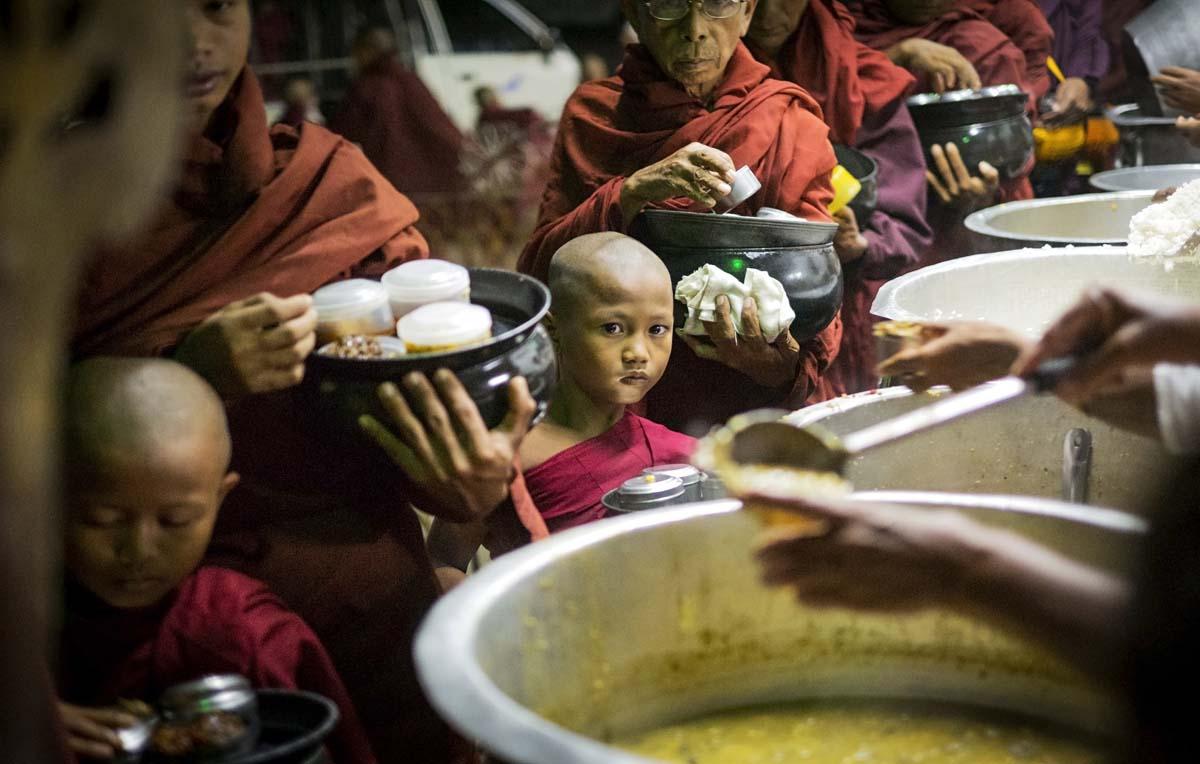 Noviisipoika odottaa ruoka-annosta varhain aamulla Nyanung Un kylässä.