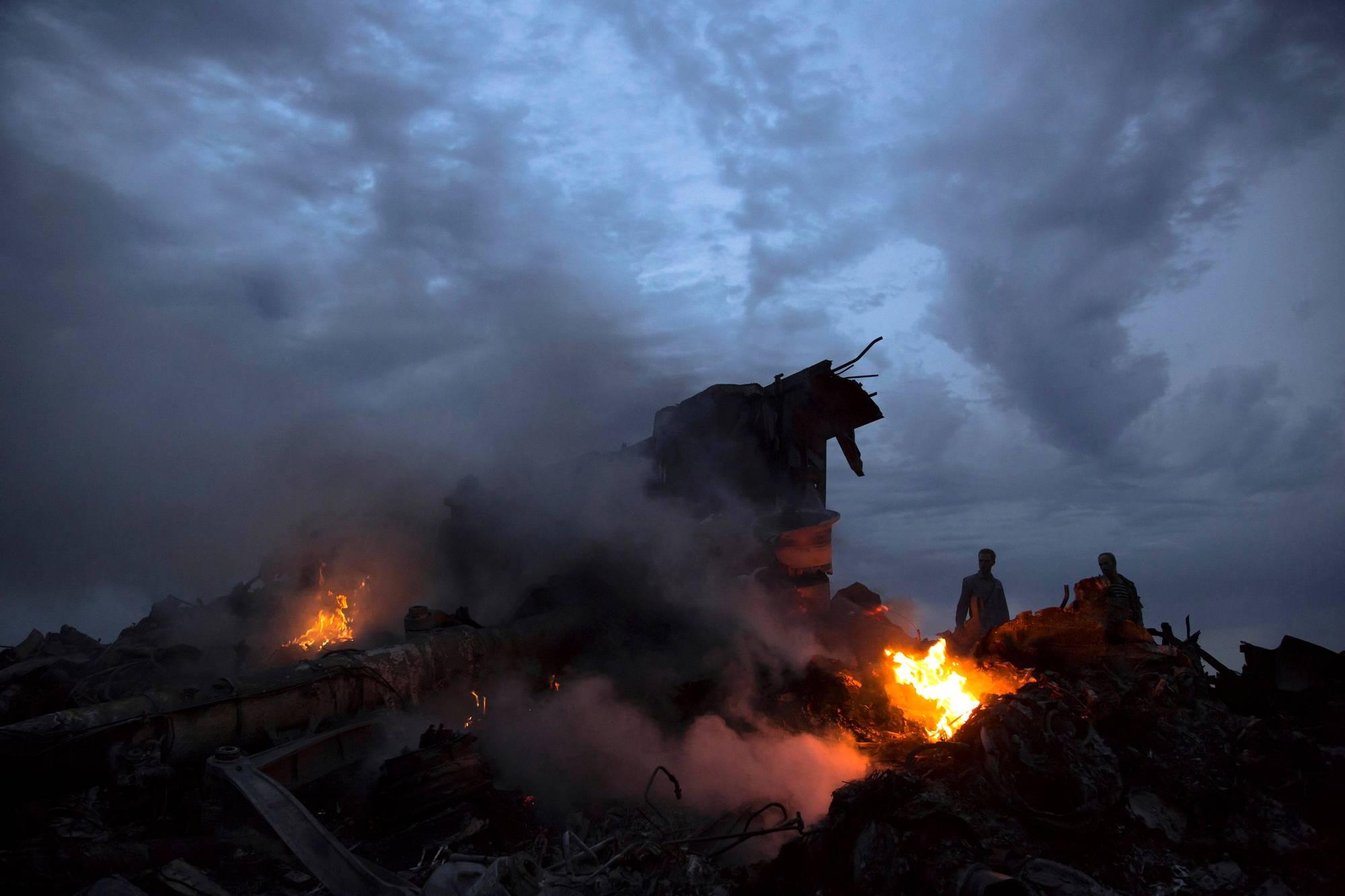 Paikalliset asukkaat tutkivat malesialais- koneen pirstaleita itäukrainalaisessa Hraboven kylässä 17. heinäkuuta 2014.