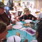 Kuvakaappaus Where To Invade Next -dokumentin trailerista. Michael Moore koululaisten ruokapöydässä.