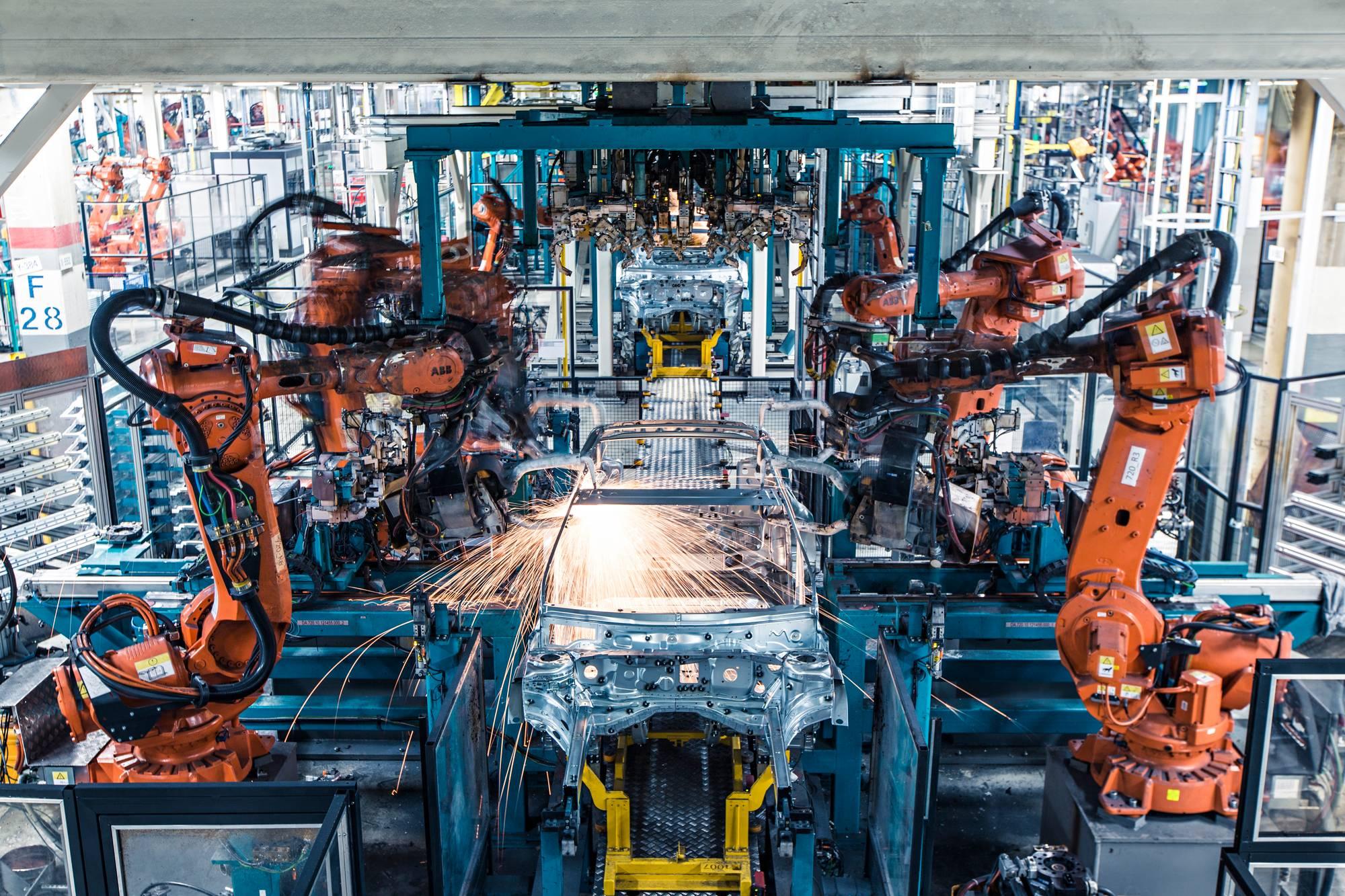 Korilinjan robottiasemalla viisi robottia pistehitsaa kyljet ja kattopalkit kiinni auton koriin.