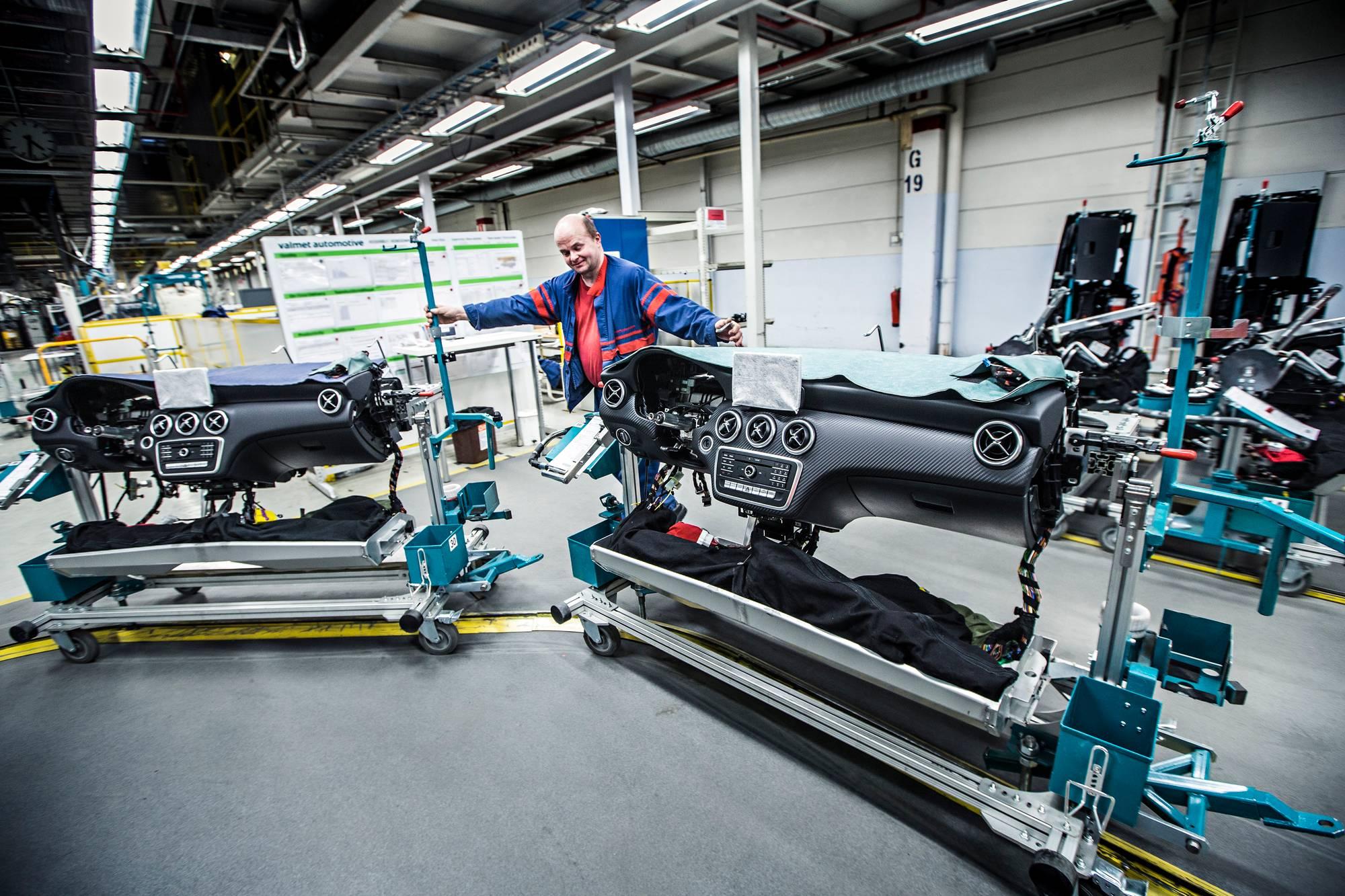 Tehtaalla vuodesta 1985 työskennellyt asentaja Antti Karppi valmistaa kojelautoja esikoonnassa, josta ne viedään kokonaisina paketteina kokoonpanolinjalle autoihin asennettaviksi.