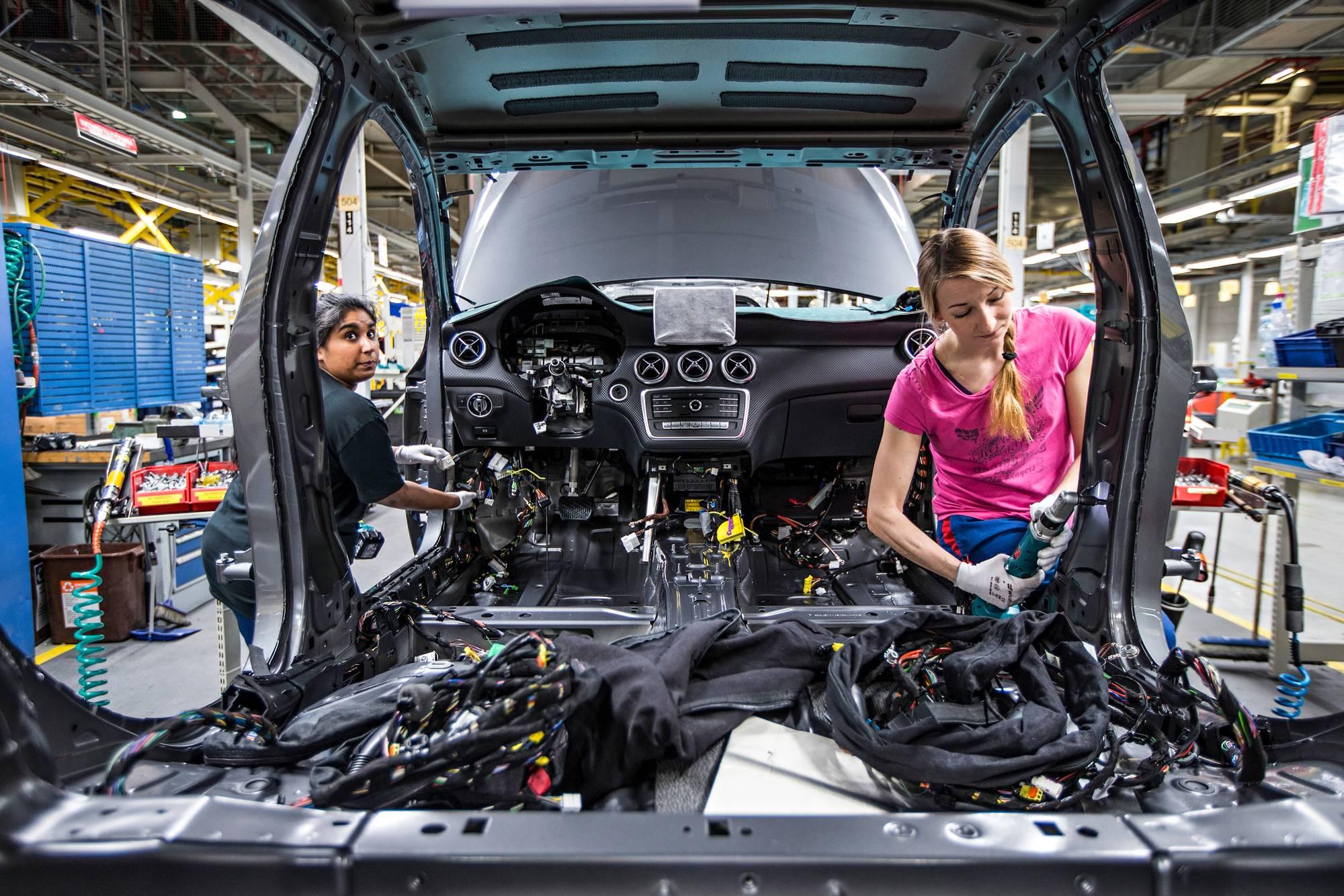 Autonasentajat Anisa Hurtig ja Tiina Lehtinen asentavat kokoonpanolinjalla johtosarjat autoihin.
