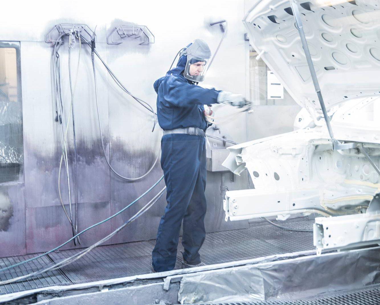 Vaikka robotteja käytetään myös maalaamossa, ihminen on monissa työvaiheissa korvaamaton. Kuvassa Veiko Lausmaa.