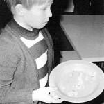 Kapitalismin vastaisuutta opetettiin leikillä: osa lapsista sai lautaselleen vain hitusen ruokaa, osa täyden annoksen. Kun klikkaat kuvan oikean yläkulman nuolia, näet kuvan kokonaan. Kohti sosialismia! -kirjan kuvitusta.
