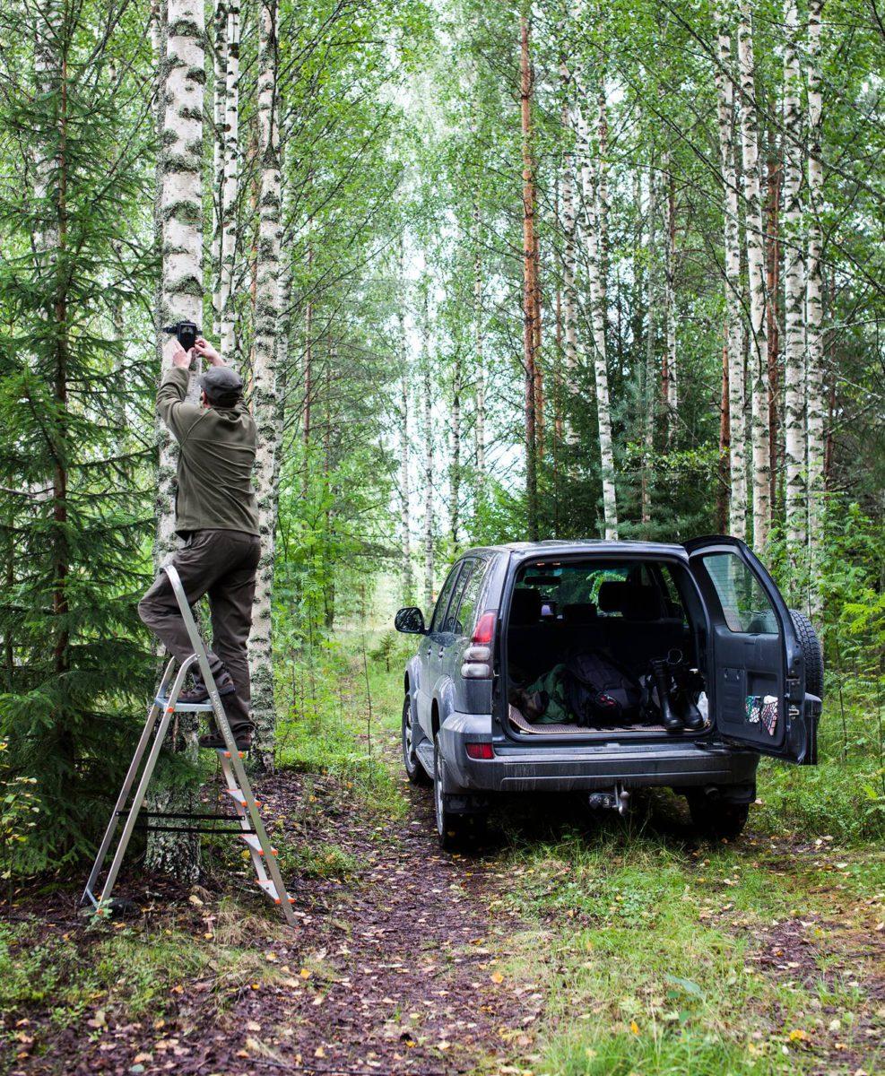 Sami Kurenniemi vaihtaa riistakameran muistikorttia Kuurnan voimalaitoksella.