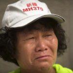 MH370-lennon matkustajan omainen itki ulkoministeriön edessä Pekingissä Kiinassa 29. heinäkuuta 2016. Hatun teksti pyytää rukoilemaan MH370:n puolesta.