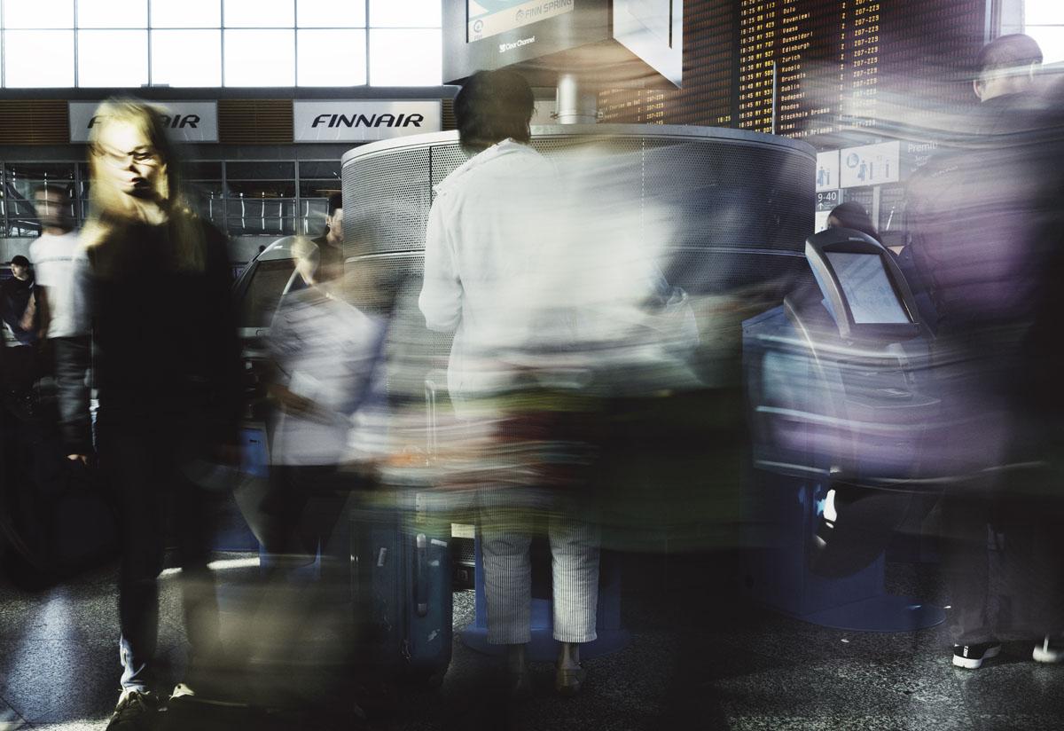 Helsinki-Vantaan lentokenttä. Matkustaja hoitaa lähtöselvityksensä automaatilla.