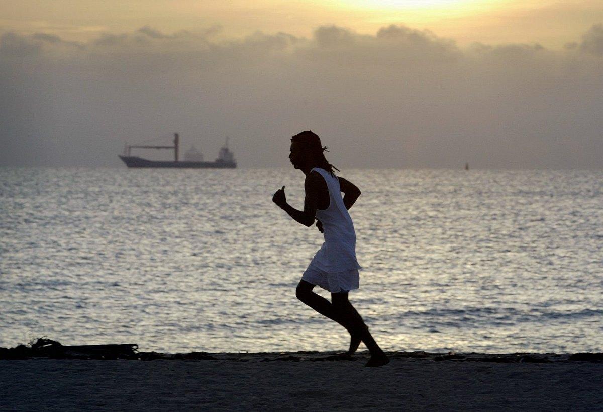 Mies juoksee rannalla.