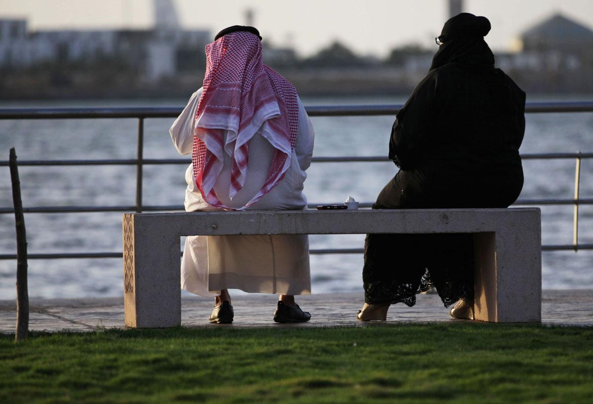 Pariskunta istuu penkillä ja katsoo merta Jeddassa Saudi-Arabiassa.