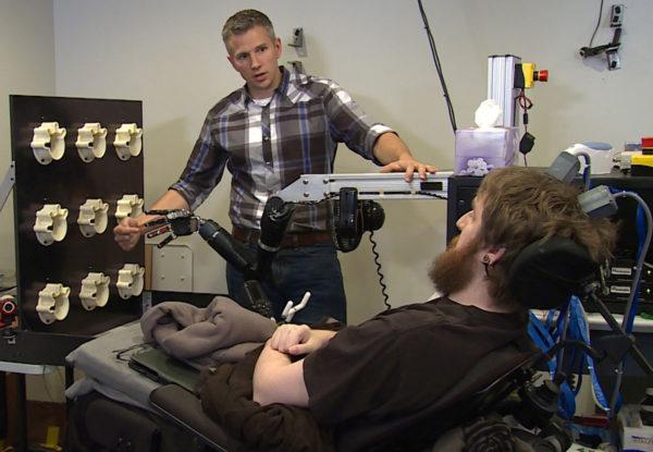 Tutkija Rob Gaunt valmistelee neliraajahalvaantunutta Nathan Copelandia aivot ja tietokoneen yhdistävään aistitestiin.