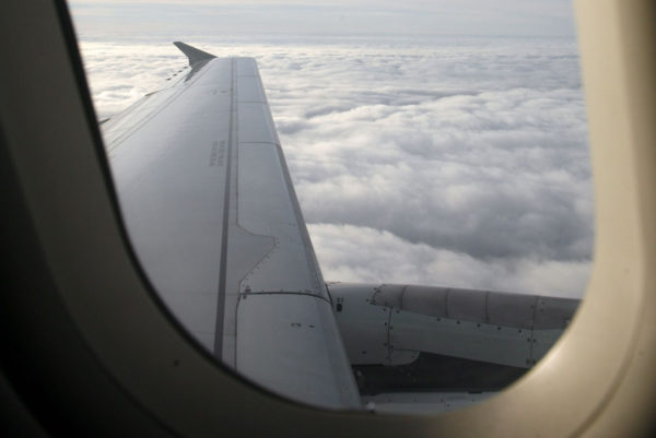 Lentokoneen ikkunanäkymä pilviselle taivaalle. Kuvituskuva.