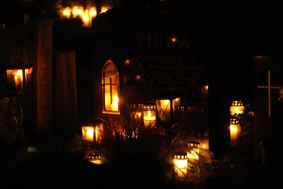 Kynttilöitä Espoon tuomiokirkon hautausmaalla pyhäinpäivänä.