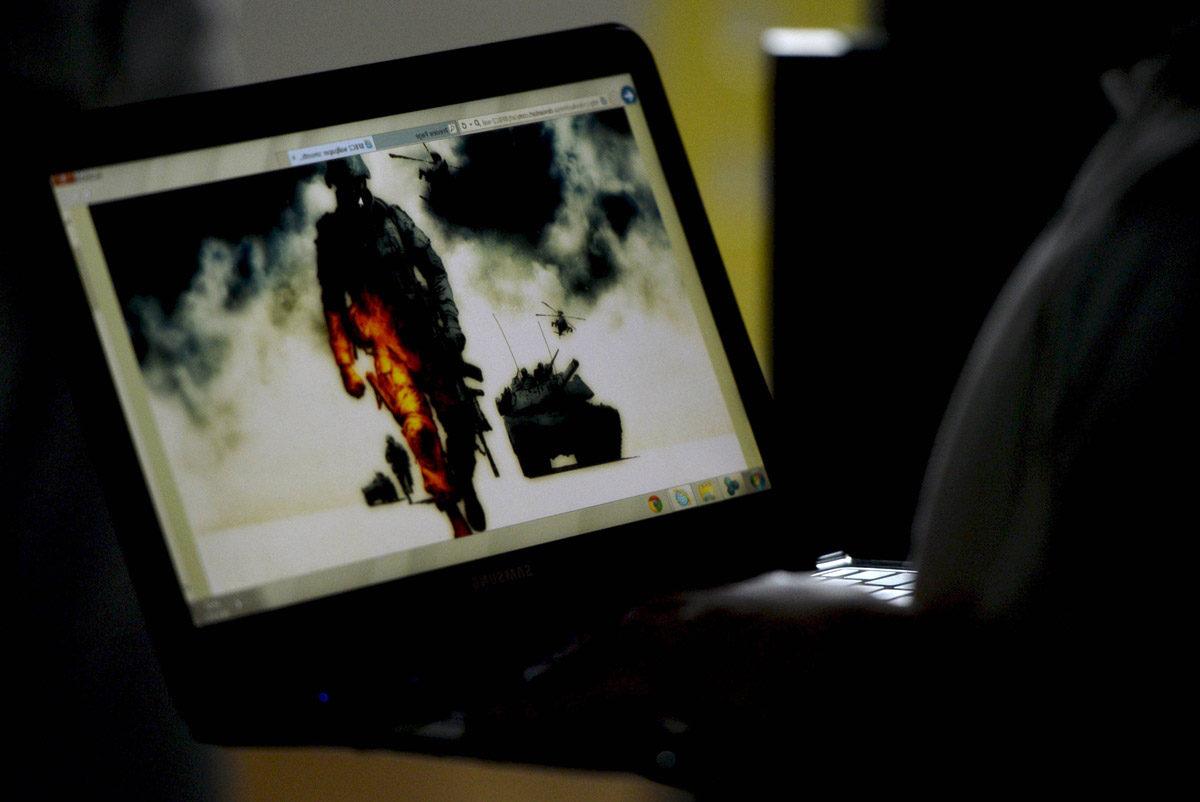 Nuori mies pelaa tietokonepeliä.