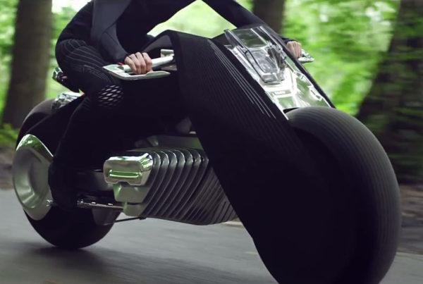 BMW:n mainosvideossa nuori nainen ajaa tulevaisuuden moottoripyörää ilman kypärää. Kuvakaappaus.