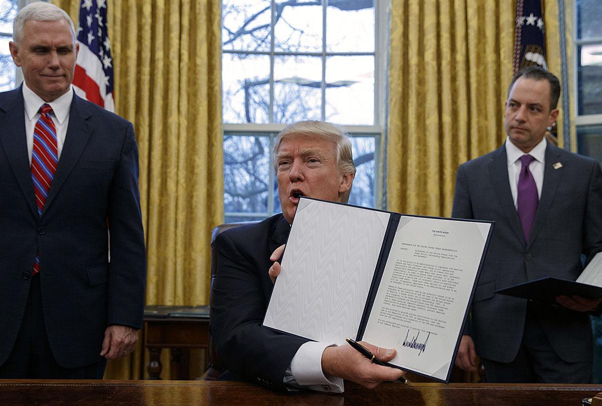 Donald Trump allekirjoitti ja varapresidentti Mike Pence (vas.) ja Valkoisen talon kansliapäällikkö Reince Priebus todistivat, kun presidentti irrotti Yhdysvallat Tyynenmeren maiden vapaakauppasopimuksesta 23. tammikuuta 2017.