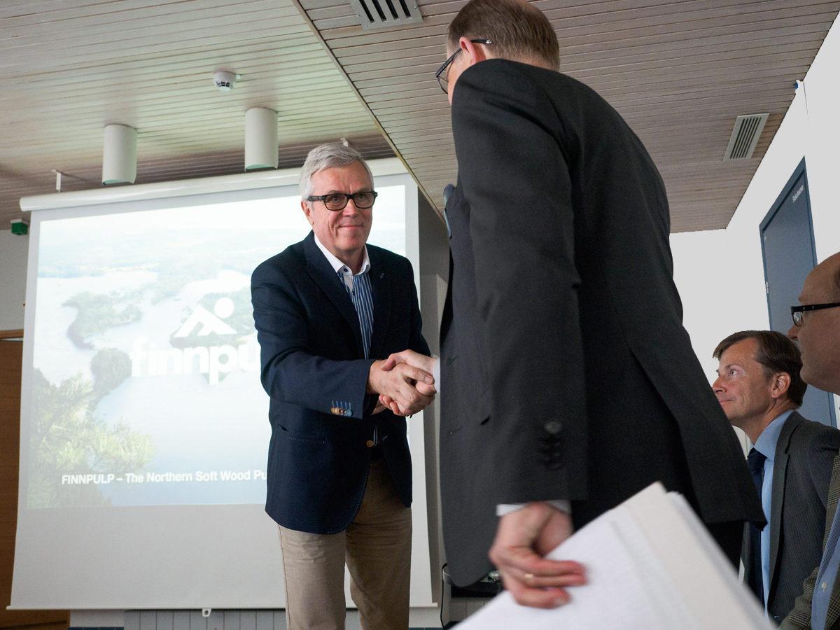 Kuopion kaupunginhallituksen puheenjohtaja Pekka Kantanen ja metsäyhtiö Finnpulp Oy:n toimitusjohtaja Martti Fredrikson kättelivät sellutehdashanketta koskevassa tiedotustilaisuudessa Kuopiossa 9. kesäkuuta 2015.