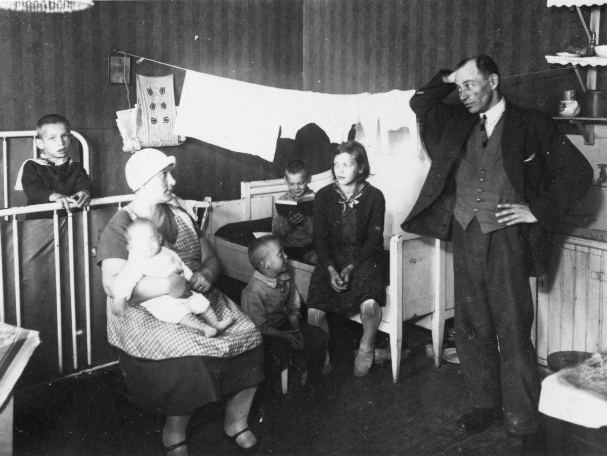 Viisilapsinen perhe kaupungin vuokra-asunnossa Helsingissä 1930-luvulla.