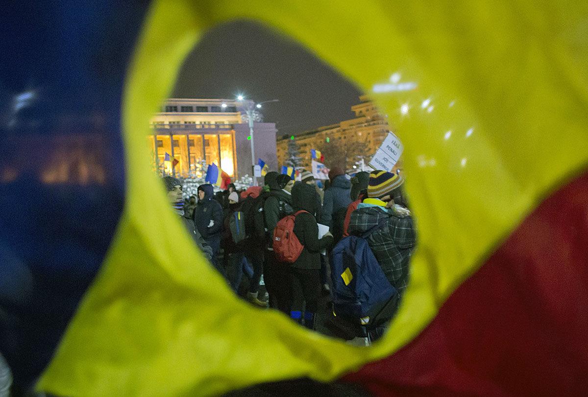 Romanian reikäinen lippu ja mielenosoittajia Bukarestissa 9. helmikuuta 2017.