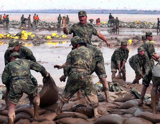 Kiinalaiset sotilaat patosivat Keltaisenjoen tulvaa hiekkasäkeillä lokakuussa 2003. Maan vajoaminen uhkaa pahentaa alueen tulvia tulevaisuudessa.