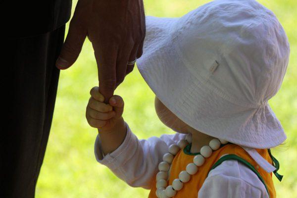 Lapsi pitää isäänsä kädestä.