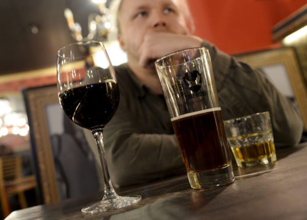 Mies juo ravintolassa. Viini, olut, viina.