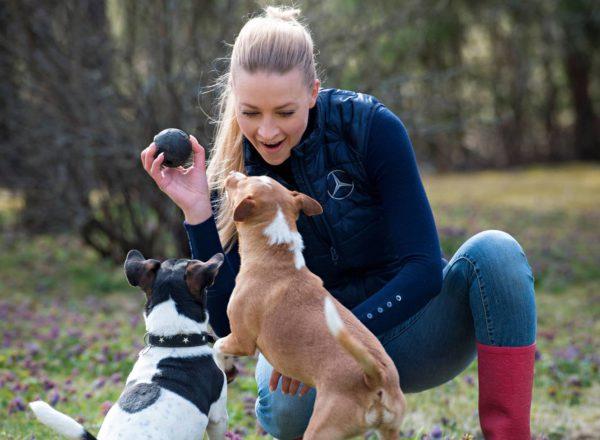 Mia Stellberg leikkii koiriensa Pepen ja Putin kanssa sukutilallaan Sipoon Linnanpellossa.