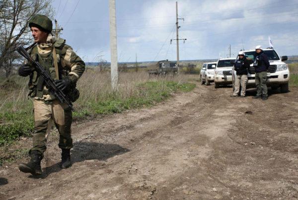 Aseistautunut Venäjä-mielinen separatistisotilas ohitti Etyj-tarkkailijoita Luhanskissa lähellä Pryshybin kylää Ukrainassa 25. huhtikuuta 2017.