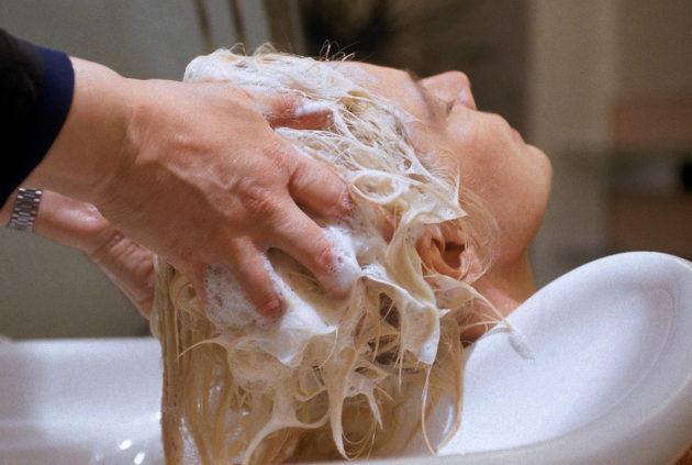 Kampaaja pesee hiuksia.