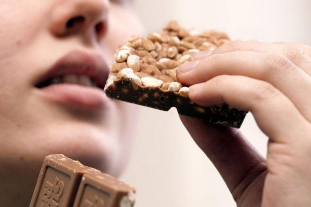 Nuori nainen syö suklaata.
