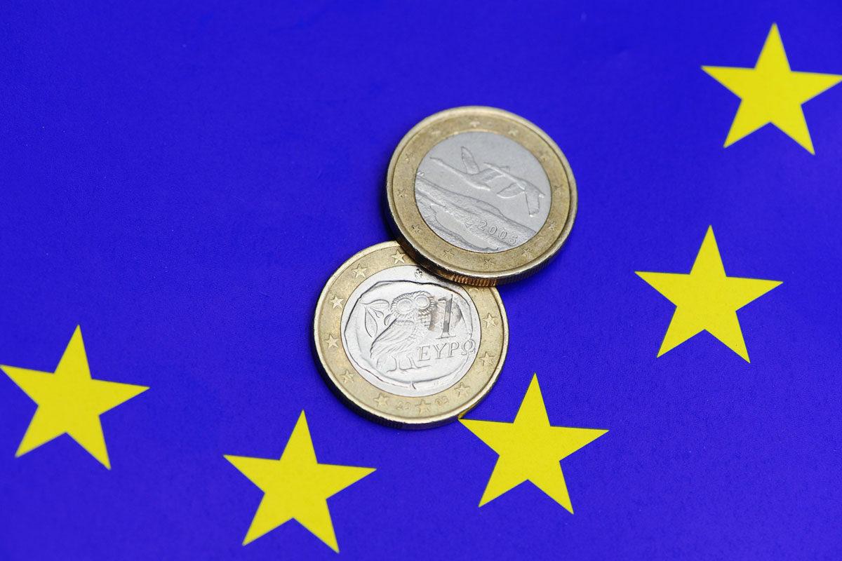 Kreikkalainen ja suomalainen yhden euron kolikko EU-lipun päällä.