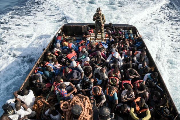 Libyan rannikkovartioston sotilas ja Välimerestä pelastettuja siirtolaisia 27. kesäkuuta 2017.