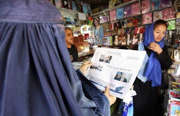 Nainen lukee Kabulissa 22. elokuuta lehtiuutista, jossa presidentti Trump kertoo uudesta strategiastaan Afganistanissa.