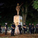Mellakkavarusteiset poliisit vartioivat Konfederaation sotilaan patsasta, joka myöhemmin poistettiin Pohjois-Carolinan yliopiston kampukselta elokuussa.