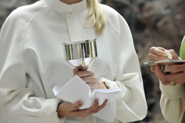 Luterilaisia pappeja jakamassa ehtoollista.