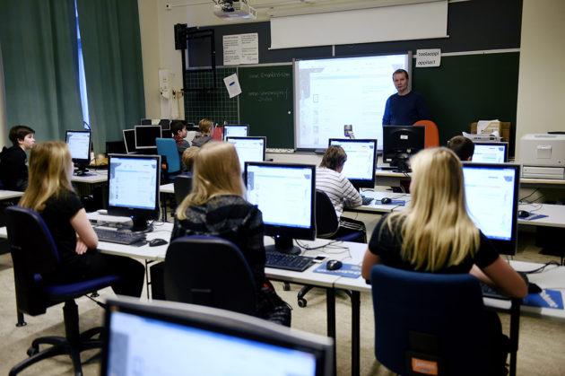 Oppilaat tutustuvat digitaalisiin oppimateriaaleihin tietokoneluokassa. Kuvituskuva.