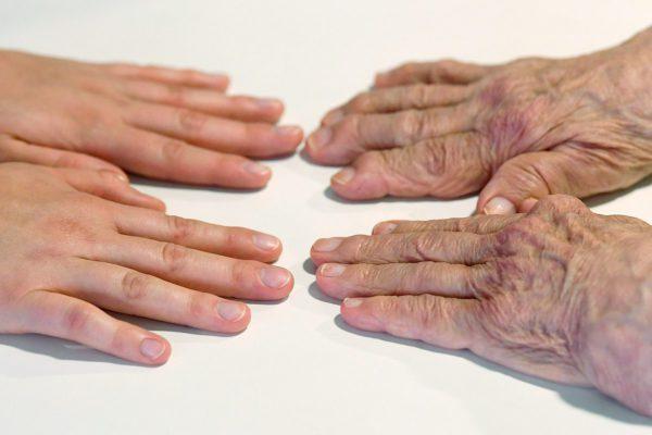 Hoitajan ja vanhuksen kädet.