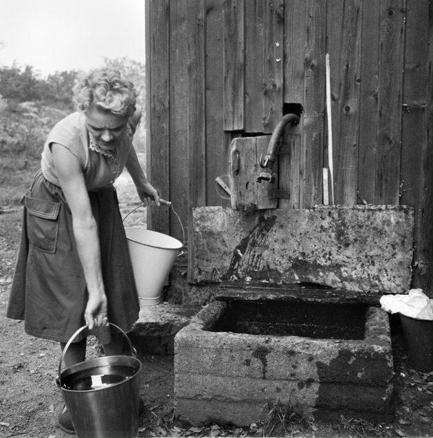 """Lempi Sini haki vettä yleisestä """"kaupunginkraanasta"""" Helsingin Hermannissa vuonna 1960."""
