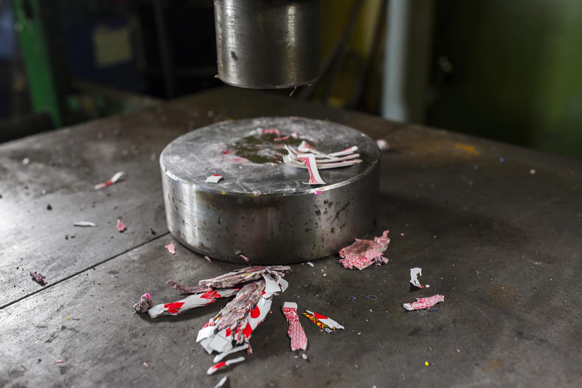 Hydraulipuristin ja murskattu korttipakka.