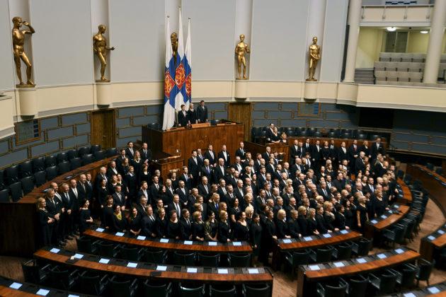 Kansanedustajat ryhmäkuvassa eduskunnan istuntosalissa joulukuussa 2017.