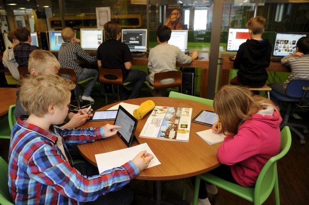 Alakoululaiset käyttävät tietokoneita. Kuvituskuva.